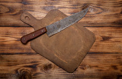 Retro cutting board and knife on old wooden burned table or boar Stock Image