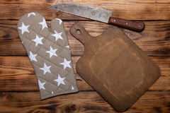 Retro cutting board, pot holder and knife on old wooden burned t Royalty Free Stock Images