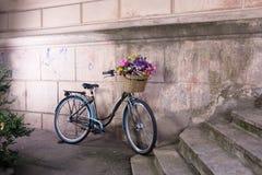retro cykel med en korg av blommor på den gamla väggen Royaltyfri Bild