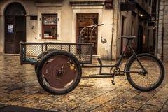 Retro cykel på tappningEuropa den medeltida plazaen med stenpavers i mulen dag under att regna höstsäsong i gammal europeisk stad royaltyfri fotografi
