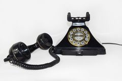 Retro czerń telefon, earpiece podnosił up i kłaść na boku - Odosobnionego obrazy stock