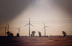 Retro dark abstract picture of wind turbines on field Royalty Free Stock Photography