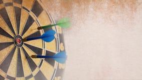 Retro darts board. Blue Dart in bull's eye. Stock Images