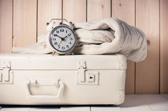 Retro decor. Beige knitted sweater, alarm clock and vintage suitcase on wooden background, retro decor Royalty Free Stock Images