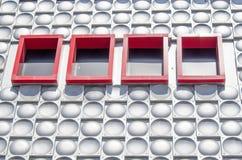 Retro decorative metal hemisphere elements and red windows. Retro decorative metal hemisphere elements on a wall and red windows Royalty Free Stock Images