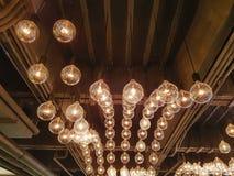 Retro dekorativt hänga exponerade ljusa kulor inom rummet arkivbild
