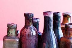 Retro design bottles macro view. Colorful dirty glass flacon set. Pink background, shallow depth of field Royalty Free Stock Photography