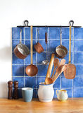 Retro design kitchen interior with accessories. Hanging copper kitchenware set. Pot, stewpot, spoon, skimmer, ladle Royalty Free Stock Image