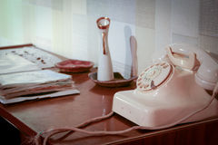 Retro desk. An retro scene of an old 1950's telephone in a contemporary setting with phone book on a side table Royalty Free Stock Image