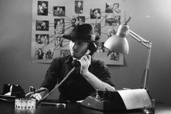 Retro detective agent 1950s style. Retro detective agent in office with important documents on office desk, 1950s style royalty free stock images