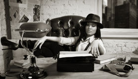 Retro detective girl sits at a table Stock Images