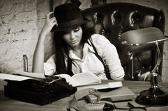 Retro detective girl sits at a table Royalty Free Stock Photos