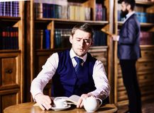 Retro detective reads book in antique room, defocused. Private investigator and detective concept. Man with calm face at tea party. Men in suit, detectives stock photo