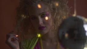 Retro discoatmosfeer, discobal en lichten, jonge blondevrouw in de jaren '80kleren stock footage