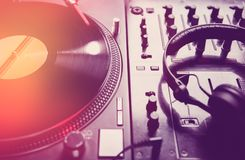 Dj turntables and sound mixer in night club. Retro dj turntable player with vinyl analog disc.Vintage record with music on turn table.Sound mixer with royalty free stock image