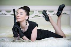 Retro donna con una pistola in una donna dell'hotel Immagine Stock