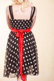 Retro dotted dress with red bow. Retro, pin up, elegant and timeless clothes concept. Woman wearing retro dotted black dress with big red bow Stock Images