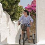 Retro- Dreirad in einer grafischen Gasse in Andros-Insel in Griechenland mit einem Frauenmodell auf die Oberseite stockbild