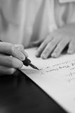 Retro effect faded and toned image of a girl writing a note with a fountain pen antique handwritten letter. stock photography