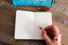 Retro effect and toned image of a woman hand writing a note with a fountain pen on a notebook. Royalty Free Stock Images
