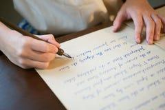 Retro- Effekt verblaßte und tonte Bild eines Mädchens, das eine Anmerkung mit einem handgeschriebenen Buchstaben der Füllfederhal Stockfotografie