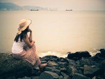 Retro- einsame und deprimierte Frau, die vor dem Meer sitzt Stockfotografie