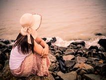 Retro- einsame und deprimierte Frau, die vor dem Meer sitzt Stockfoto