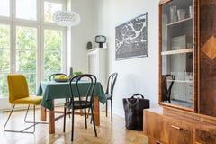 Retro- Esszimmerinnenraum mit einer Tabelle, Stühlen und Schrank in einer Wohnung lizenzfreies stockfoto
