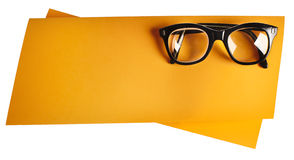Retro eyeglasses with black frame on orange creative support. Retro eyeglasses with black frame on creative support made of orange paper, photographed on white stock images
