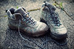 Retro Faded Photo Of Dirty Walking Boots on Sidewalk. With use of colour filters royalty free stock photos