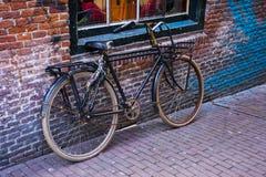 Retro- Fahrrad geparkt gegen eine Backsteinmauer Lizenzfreie Stockfotos