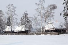 Retro farmhouse winter. Old hauses with snow on the roof. Museum in kolbuszowa, Poland Royalty Free Stock Photo