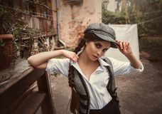 Retro fashion girl. Young girl retro hooligan in a cap. A woman is dressed like a man, a vintage style. Times of the Great Depression stock image
