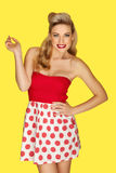 Retro fashion model in red polka dots. Glamorous blonde retro fashion model in a red polka dot miniskirt with vivid red lipstick and an olden day coiffure posing Royalty Free Stock Photography