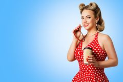 Retro Fashion Model Red Polka Dots Dress, Woman Pinup Beauty Style, Happy Girl Holding Paper Cup. Over blue background stock photos