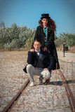 Retro fashionable woman and man standing on railroad in vintage Royalty Free Stock Images