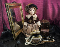 Retro fashioned porcelain doll with jewelry box. Royalty Free Stock Images