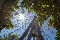 Retro- Ferris Wheel auf blauem bewölktem Himmel und Sonneneruption Stockfotos