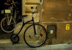 Retro fiets met wielen van verschillende grootte dichtbij de muur royalty-vrije stock afbeelding