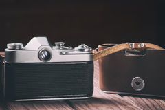 Retro film camera with case on wood and black background. Vintage toned and selective focus Royalty Free Stock Photos