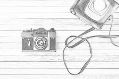 Retro film camera. With coffer on a wooden background. Simulation of a pencil drawing Stock Image