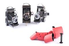 Retro film 120 med den plast- rullen för retro kameror för medelformat på vit bakgrund med skuggor, tre oskarpa retro kameror på Arkivbild