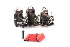 Retro 120 film for medium format retro cameras on white background with shadows, three blurry vintage cameras on background, can m. 120 film for medium format stock photography