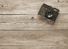 Retro film photo camera. On the wooden background Royalty Free Stock Images