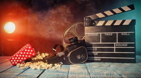 Retro film production accessories still life. Retro film production accessories placed on wooden planks. Concept of film-making. Smoke effect with spot light on Royalty Free Stock Photos
