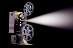 Retro filmprojektor med den ljusa strålen på svart Arkivbilder