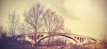 Retro filter picture of an arch bridge over river.  Stock Photo