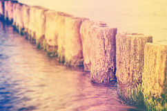 Retro filtered blurred abstract background, shallow depth of fie. Retro filtered blurred abstract background made of wooden posts in water, shallow depth of royalty free stock photography
