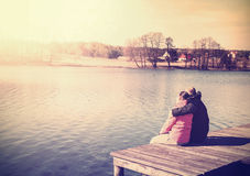 Retro filtered photo of a couple sitting on pier. Stock Photography