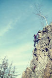 Retro filtered photo of female rock climber. Stock Photo